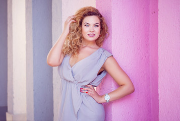 blond girl model plus size on the background of a pink wall