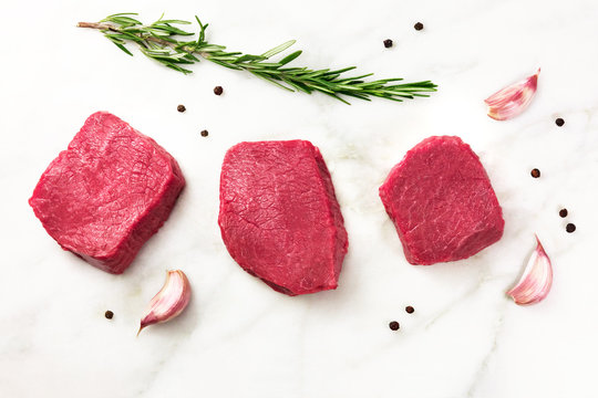 Three slices of raw meat with seasoning and copyspace