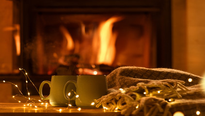 Steam from a cups with a hot cocoa on the fireplace background.   Decoration garlands of lights .