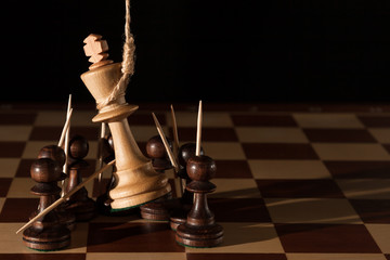 Chess. White king on the hinge loop lynch among the black figures on the chessboard