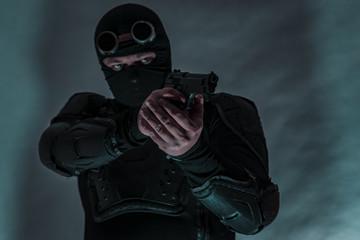 Armed spy in bulletproof vest. The gun is aimed at the target.
