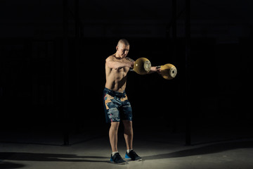 A strong man picks up kettlebell in gym. Kettlebell lifting. Sportlife