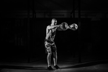 A strong man picks up kettlebell in gym. Kettlebell lifting. Black and white conception