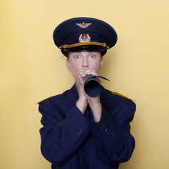navy woman in uniform in studio on yellow background blowing or calling