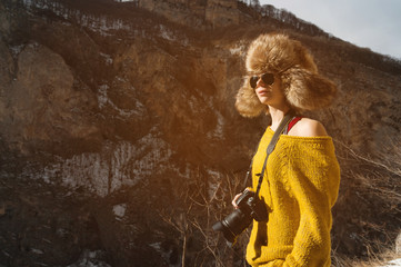 A girl photographer in sunglasses and a big fur hat and a yellow knitted sweater stands against the background of high rocks in the gorge with a dslr camera her in hand.