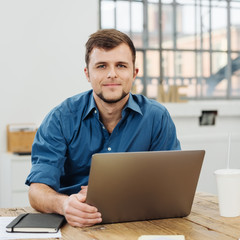 Smiling man sitting in front of laptop