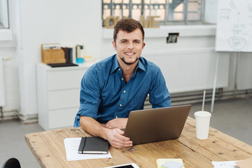 Young cheerful man working with laptop