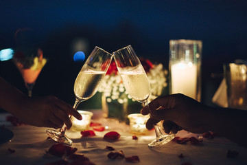 Romantic candlelight dinner table setup. Man & Woman hold glass of Champaign.