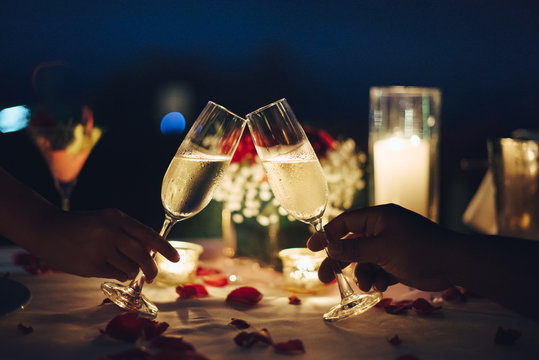 Romantic candlelight dinner table setup for couple with beautiful light as background. Man & Woman hold glass of Champaign. Concept for valentine's day and date.