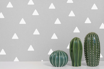 White desk with three ceramic cacti on the background of the wall in a white triangles wall in a circle