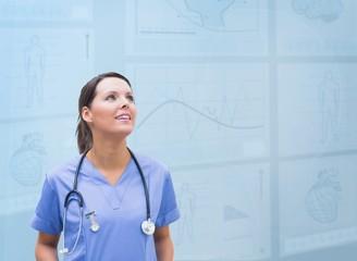 Nurse looking up against blue digital background