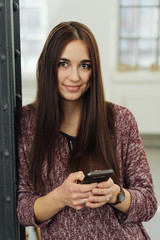 Attractive smiling woman holding a smartphone