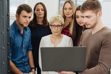 Group of people in front of laptop at office