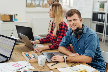 Young man with headphones working in a business team
