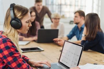 Young businesswoman working wearing headphones