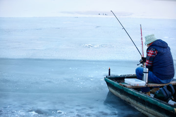Back view o fisherman in boat while fishing in winter