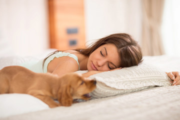 Young girl sleep with her puppy in bedroom