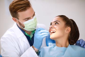 Dentist examine girl's teeth with mirror