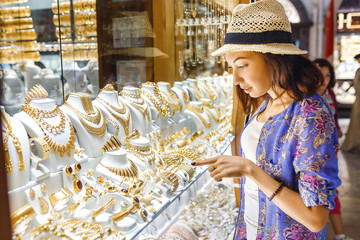 Eastern woman choose golden jewelry at shop