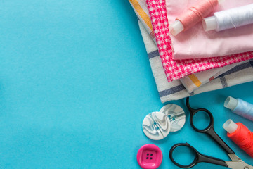 Multicolored threads, scissors, buttons, fabric and various sewing accessories on a blue background with copy space flat lay