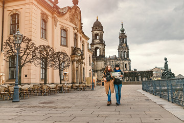 Two charming cheerful women are walking with a map along Dresden Street, Germany. The concept of love and friendship in travel