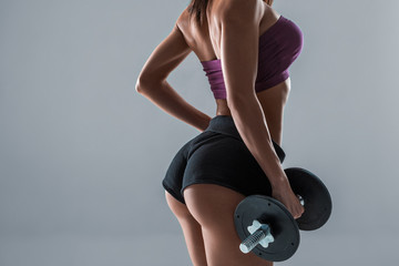 Strong muscular young woman holding dumbbells at her side standing with her back to the camera looking to the side, on grey with copy space