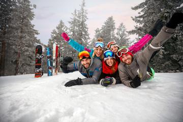 Enjoying in beautiful winter day- skiers lying on snow and having fun