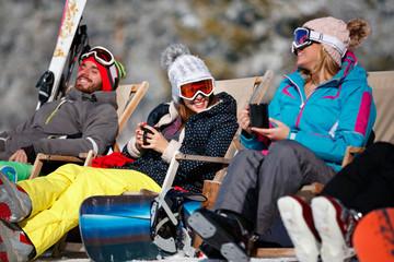 female friends enjoying hot drink in cafe at ski resort. Sunbathing in snow