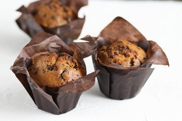 A chocolate muffins in brown paper on a white background.
