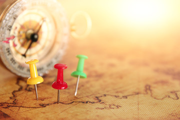 Image of pins attached to map, showing location or travel destination next to vintage compass. selective focus.