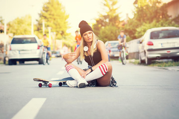 Cool skater girl in street style, sitting on the street posing with skate board in urban environment