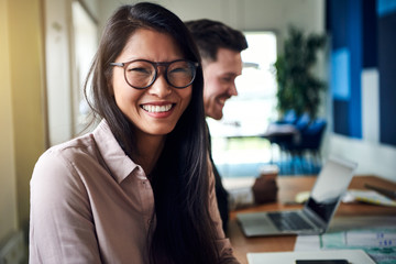 Smiling young Asian businesswoman sitting with colleagues in an office