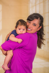 Close up of young mother is holding her little baby, mom wearing a purple blouse and baby blue clothes, in a blurred background