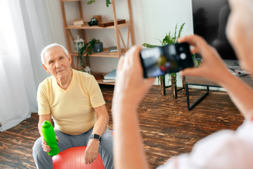 Senior couple exercise together at home taking pictures with water bottle close-up