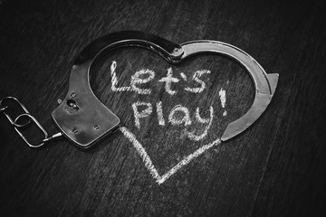 Lets play bdsm. Handcuffs for role-playing. Adult game concept. Handcuffs like heart with caption on black background.