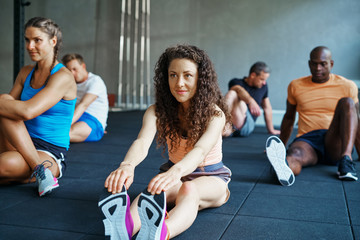 Fit young woman stretching during a gym class warmup