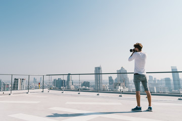 Young white Caucasian man taking cityscape photo on building rooftop on sunny day. Photography hobby, gadget technology, or leisure activity concept. With copy space on blue sky