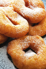 Donuts with powdered sugar on a dark background