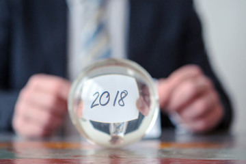 man holding paper with the numbers 2018 in front of glass ball