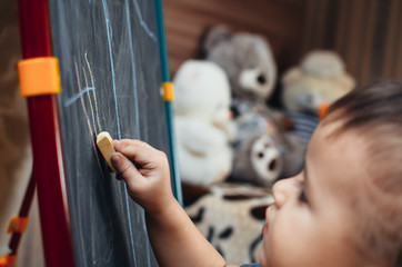 a young three year old boy drawing with chalk on a blackboard on an easel, at home in my room