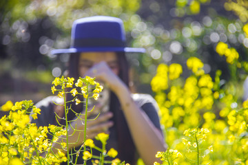 Woman tourist taking photo of yellow flowers with smartphone