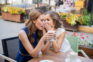 smiling young women drinking coffee and gossiping