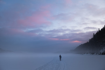 Skiing on a frozen, misty lake. New moon behind coloured evening skies
