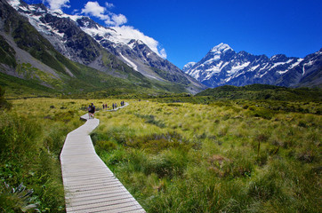 Beautiful landscape of walkway in the nature, mountains in the background. Walking the Hooker Valley Track, Mount Cook, New Zealand. Enjoy the summer. Hiking and walking in the nature.