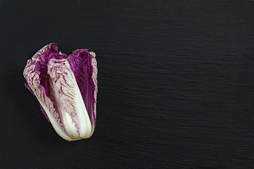 Blue napa cabbage on black stone surface. Top view, copy space.