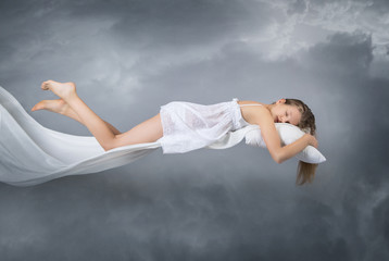 Sleeping girl. Flying in a dream. Clouds on grey background. Sleep