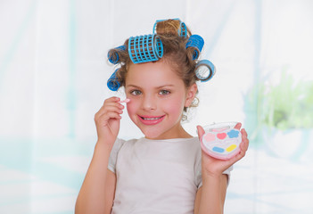 Close up of little girl using make up while wearing hair-rollers and bathrobe in a blurred background