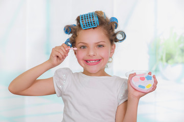 Close up of little beautiful girl using make up while wearing hair-rollers and bathrobe in a blurred background
