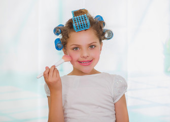 Little girl using a brush to make up while wearing hair-rollers and bathrobe