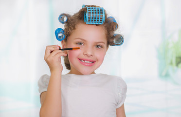 Little girl using a eye mascara in her eye while wearing hair-rollers and bathrobe in a blurred background